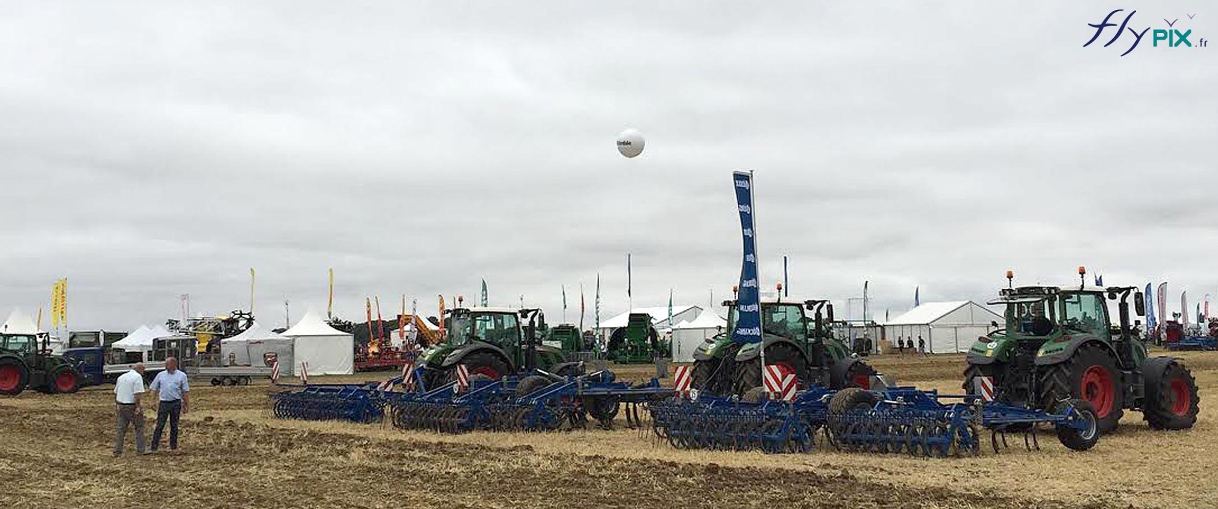 Un ballon personnalisé gonflé à l'hélium survole un stand d'exposition de matériel agricole.