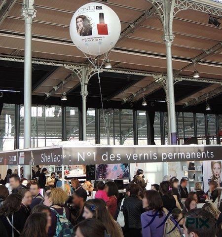 Ballon hélium publicitaire sphérique avec marquage personnalisé en impression numérique sur fond blanc, survol d'un stand.