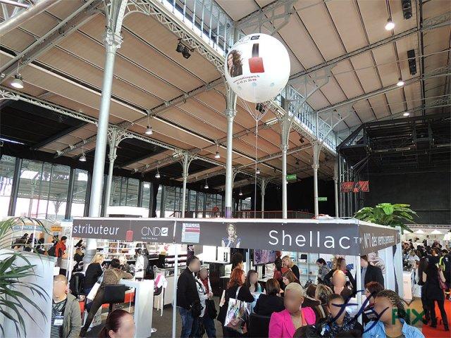 Ballon publicitaire sphérique à hélium survolant des stands pendant un salon.