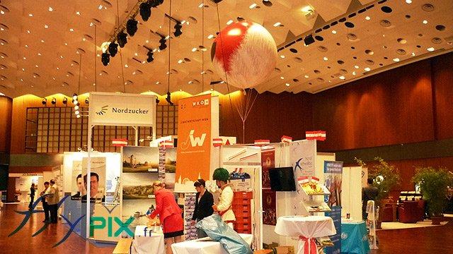 Ballon publicitaire sphérique gonflé à l'hélium survolant un stand pendant une exposition