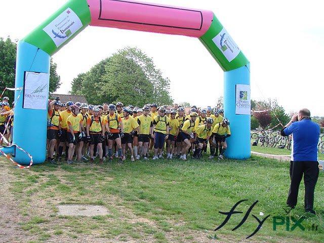Arche publicitaire personnalisée déployée pendant une compétition sportive, ici une course à pied. Ici, la ligne de départ avec les coureurs.