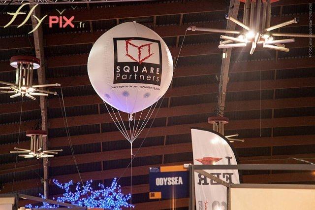 Ballons sphériques publicitaires en PVC 0,18 mm, avec marquages en impression numérique couleur full print, volant au dessus d'un stand lors d'un salon professionnel.