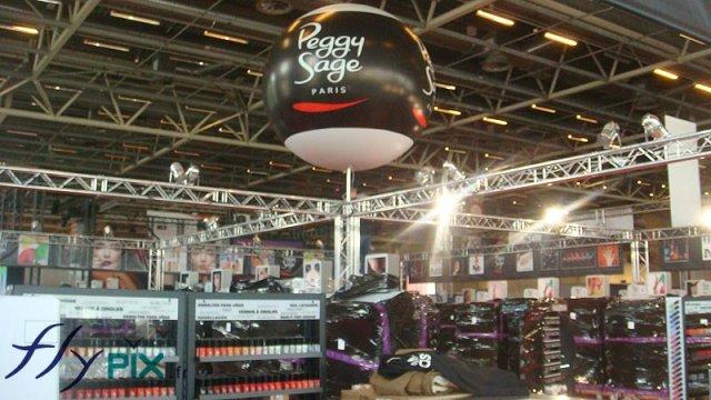 Ballon PVC sur mât télescopique en aluminium posé pendant un stand lors d'un salon professionnel.