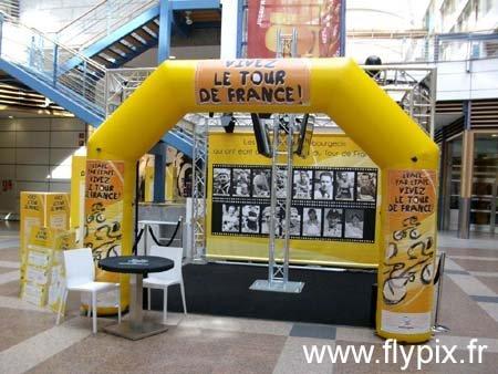 Exemple d'utilisation d'arche publicitaire gonflable pour un stand présentant le Tour de France pendant une foire à l'occasion d'un événement sportif.