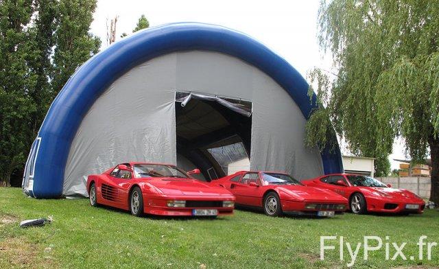 Voitures Ferrari posant devant une tente gonflable publicitaire, en extérieur, créée pour un concessionnaire auto, pour une exposition sur les voitures (salon de l'automobile).