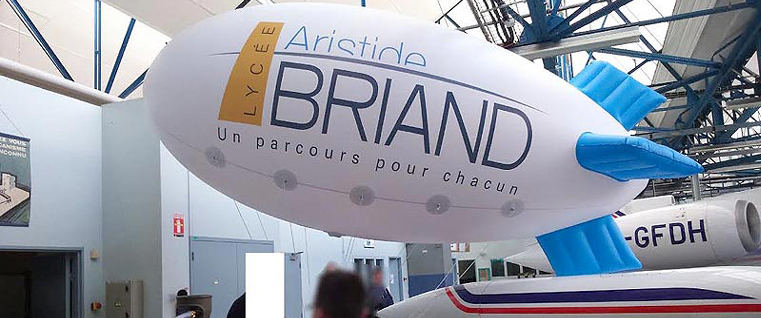 Ballon dirigeable zeppelin publicitaire doté d'un logo sur fond blanc imprimé en couleur.